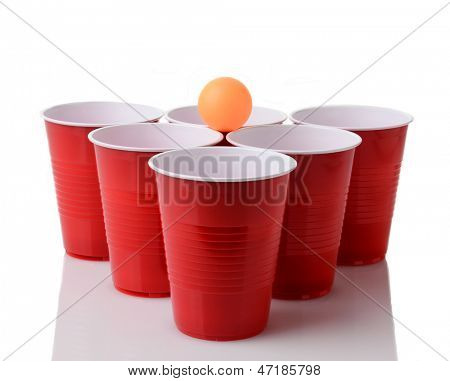 A yellow ping pong ball resting on a group of red plastic cups arranged for playing Beer Pong isolated on a white background with reflection.