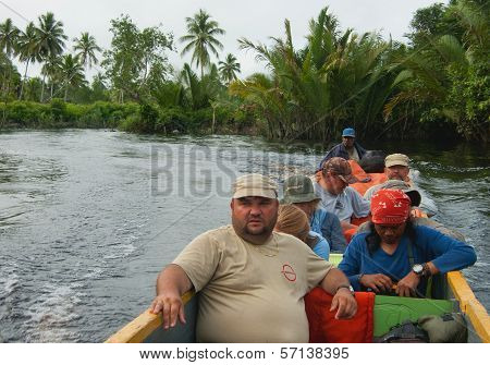 The Group Of Tourists Floats On A Wooden Canoe Down The River.