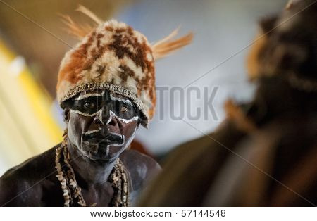 The Portrait Asmat Warrior With A Traditional Painting And Coloring On A Face.