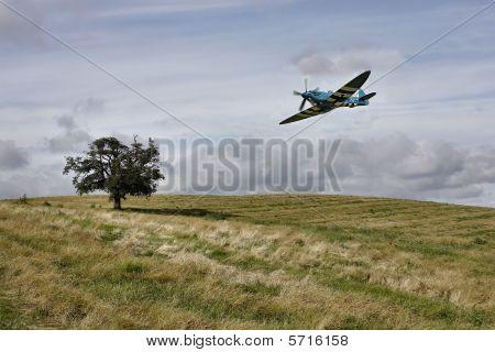 Spitfire flying over farmland
