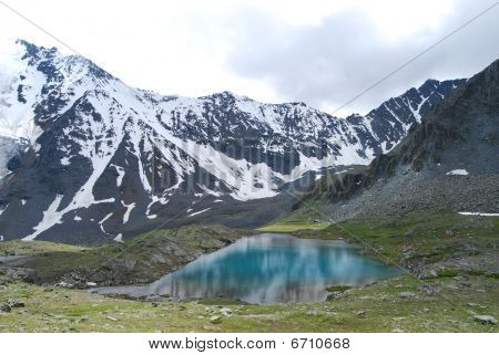 turquoise lake in front of snowed hills