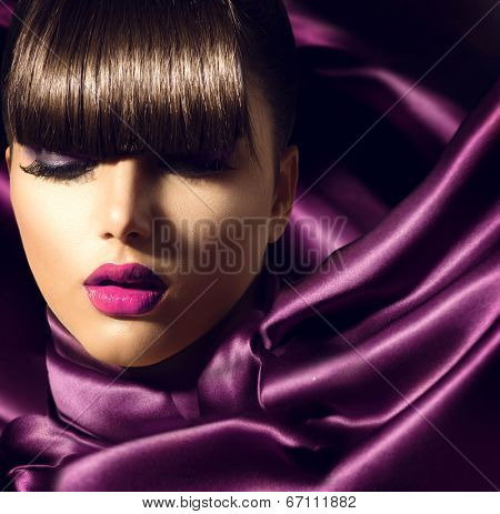 Fringe. Fashion Model Girl With Trendy Hairstyle. Haircut. Stylish Beauty Brunette Woman on violet silk fabric. Beautiful Make up. Vogue Style. Hair cut poster