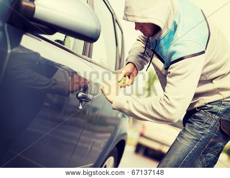 transportation, crime and ownership concept - thief breaking the car lock poster