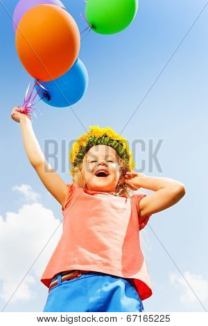 Positive girl with balloons wears flower circlet