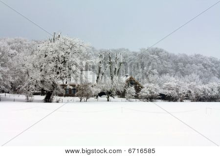 A Farm In A Frosted Winter Forest