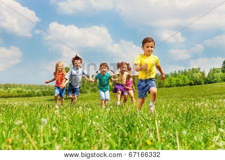 Running kids in green field during summer
