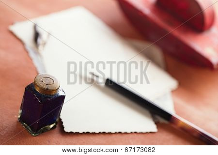 vintage red leather ink blotter  with retro post cards on leather table, shallow dof poster