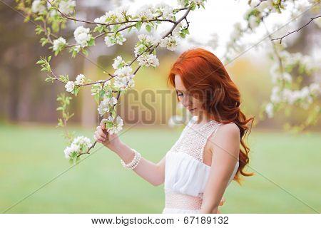 Beautiful woman near the flowering tree