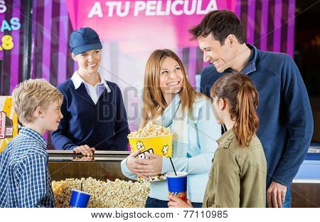 Happy family of four buying snacks from female seller at concession stand in cinema