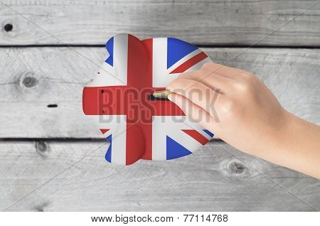 United Kingdom Saving Concept With Little Hand Dropping A Coing Into Piggy Bank Overlaid With Uk Fla