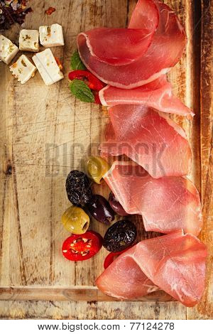meat platter of Cured Meat and olives on old wooden board poster