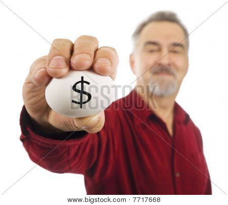 Mature Man Holds An Egg With A Dollar Sign ($) Written On It.