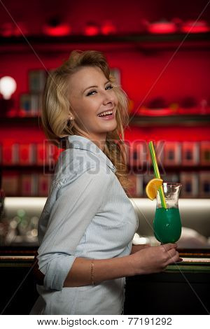 Preety Young Woman Drinks Cocktail In A Night Club