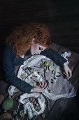 The red-haired witch preparing a potion from a variety of ingredients, spread on a wooden table. Picture toned. poster
