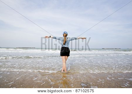 Portrait Of Young Woman On The Beach Near The Sea Standing With Hands Up Wearing Blue Shirst, Black