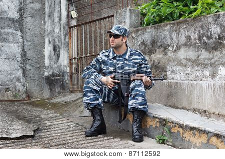 Caucasian Military Man With Black Sunglasses In Urban Warfare Sitting With Rifle