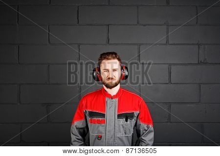 Man Wearing Overalls With Professional Earplug On Brick Wall