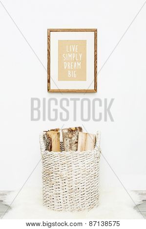 wooden frame LIVE SIMPLY DREAM BIG. Hipster scandinavian style room interior. Busket with firewood and a sheep rug on the floor poster
