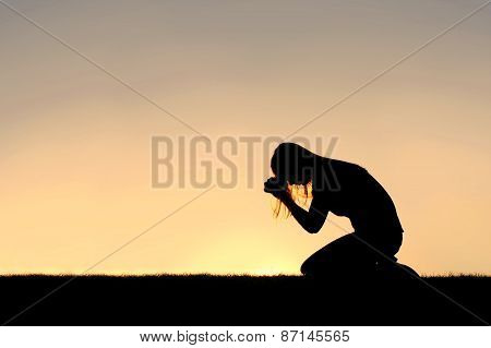 A silhouette of a young Christian woman is bowing her head in prayer and desperation outside during sunset. poster