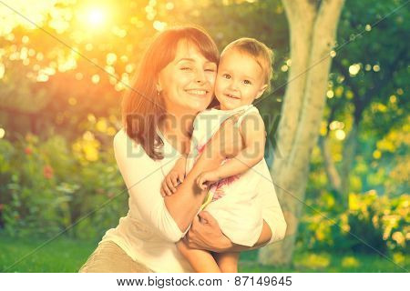 Beautiful Mother And Baby outdoors. Nature. Beauty Mum and her Child playing in Park together. Outdoor Portrait of happy family. Joy. Mom and Baby  poster