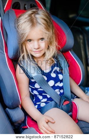 Adorable Smiling Little Girl With Long Blond Hair Buckled In Car Seat Looking Through The Car Window