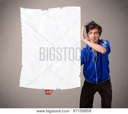 Attractive young boy holding crumpled white paper copy space