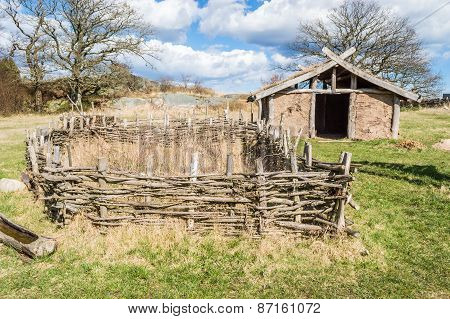 Part of viking age village replica in southern Sweden in early spring. Small farm fields are fenced in with juniper branches for protection against farm animals. Clay house in background. poster