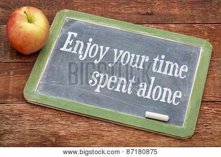 Enjoy your time spent alone - positive words on a slate blackboard against red barn wood