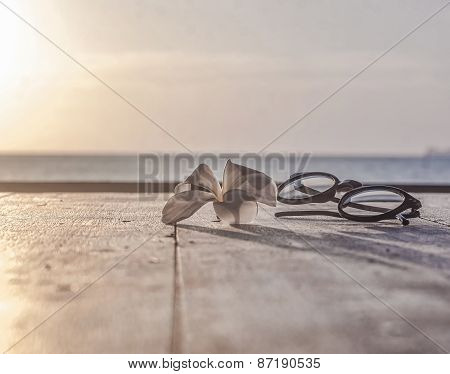 glasses and lotus flower lying on a wooden table