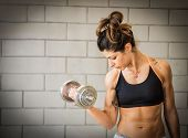 Woman working out with dumbell - Sportive girl training her bicep poster
