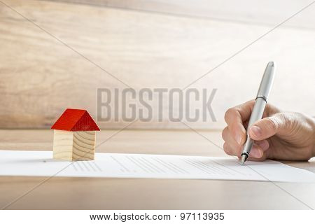 Closeup Of New Homeowner Signing A Contract Of House Sale Or Mortgage Papers