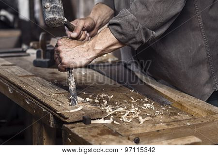 Carpenter With A Hammer And Chisel