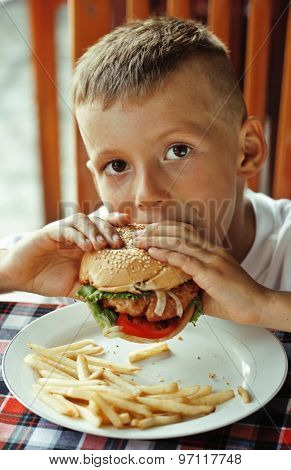 little cute boy 6 years old with hamburger and french fries  in restaurant close up poster