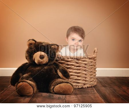 A little baby is sitting on a basket with a teddy bear on a studio brown background for a photography or babysitting concept.