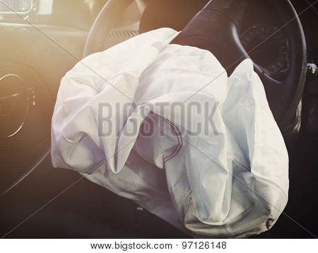 A front car airbag has deflated in a steering wheel from an accident. Use it for a safety or insurance concept.