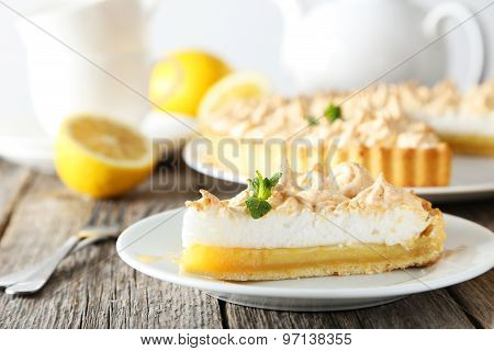 Fresh and tasty lemon meringue pie on wooden table