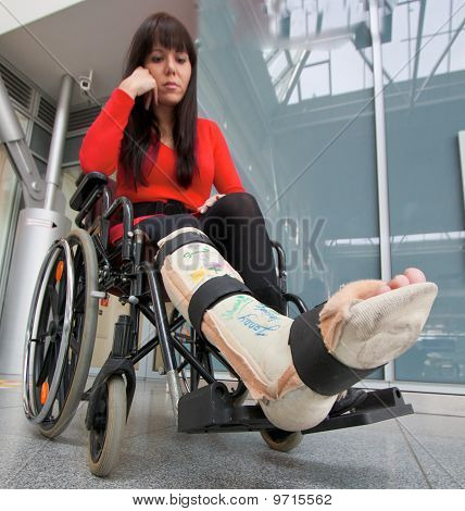 Young woman with a leg cast and wheelchair in the hospital poster