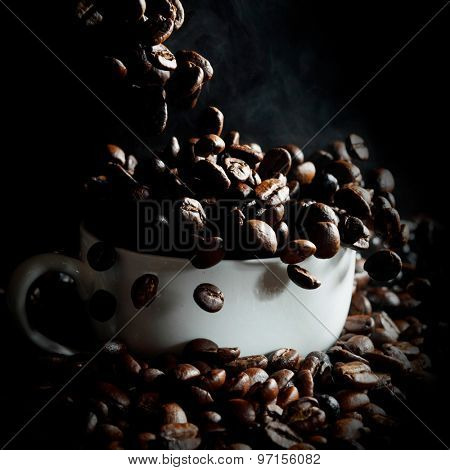 Cup filled with hot fresh steaming coffee beans on black