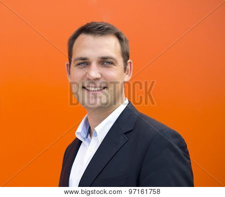 Close up portrait of a young business man in a dark suit and white shirt, against the backdrop of an orange wall