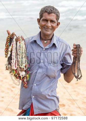Sri Lankan man sells jewelery to tourists on the white sand beach. Hawking is a livelihood popular
