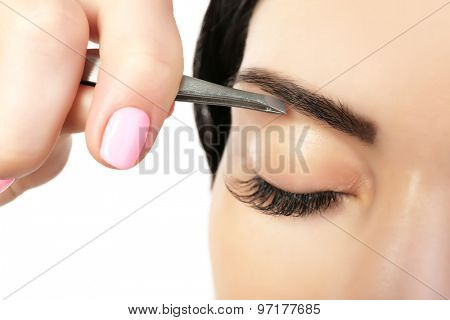 Young woman plucking eyebrows with tweezers close up