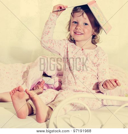 Beautiful Little Girl In The Crib With A Book On Your Head.