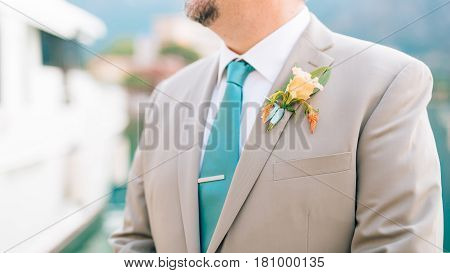 The groom with a beard boutonniere on the lapel of a light jacket with a blue tie.