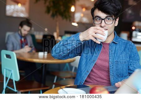 Portrait of casual young man wearing glasses and jeans jacket drinking coffee  while working with laptop and smartphone at table in cafe