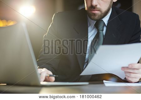 Portrait of modern bearded businessman working in office using laptop and reviewing documentation