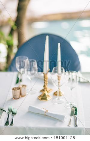 Candles on the table in the restaurant. Table setting in a cafe. Romantic dinner.