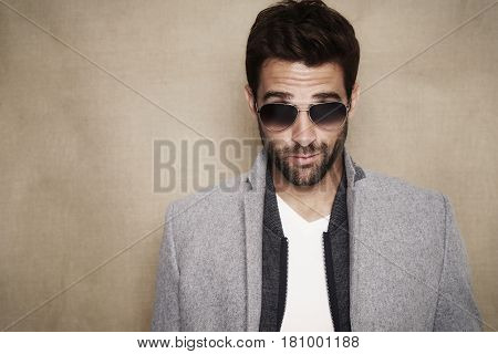 Sunglasses guy in grey coat portrait studio