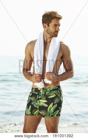 Flower shorts on dude holding towel at sea