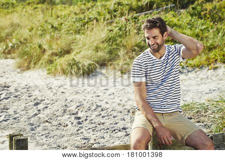 Laughing man on beach in shorts and striped top