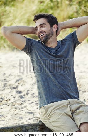 Handsome summer Beach dude in t-shirt relaxes smiling